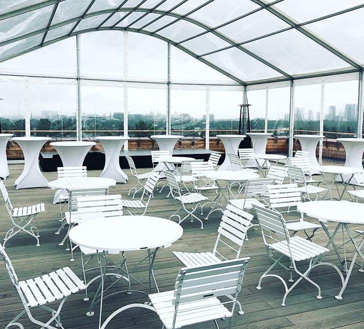 Kaarkatusega telk katuseterrassil valge mööbliga
